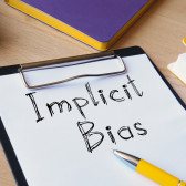 What is an implicit bias and how does it impact human behavior?
